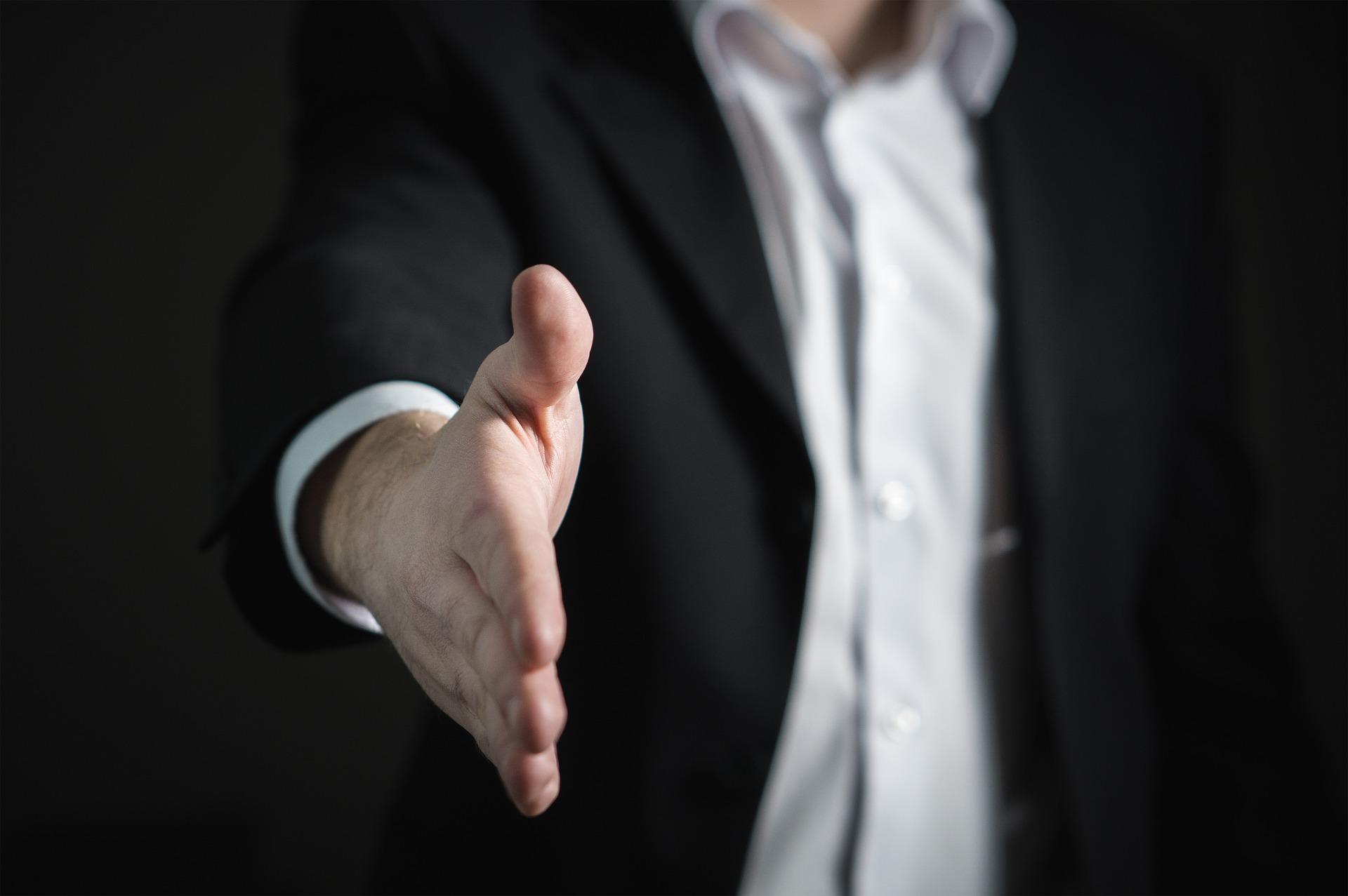 握手しようと手を伸ばすスーツの男性の手元