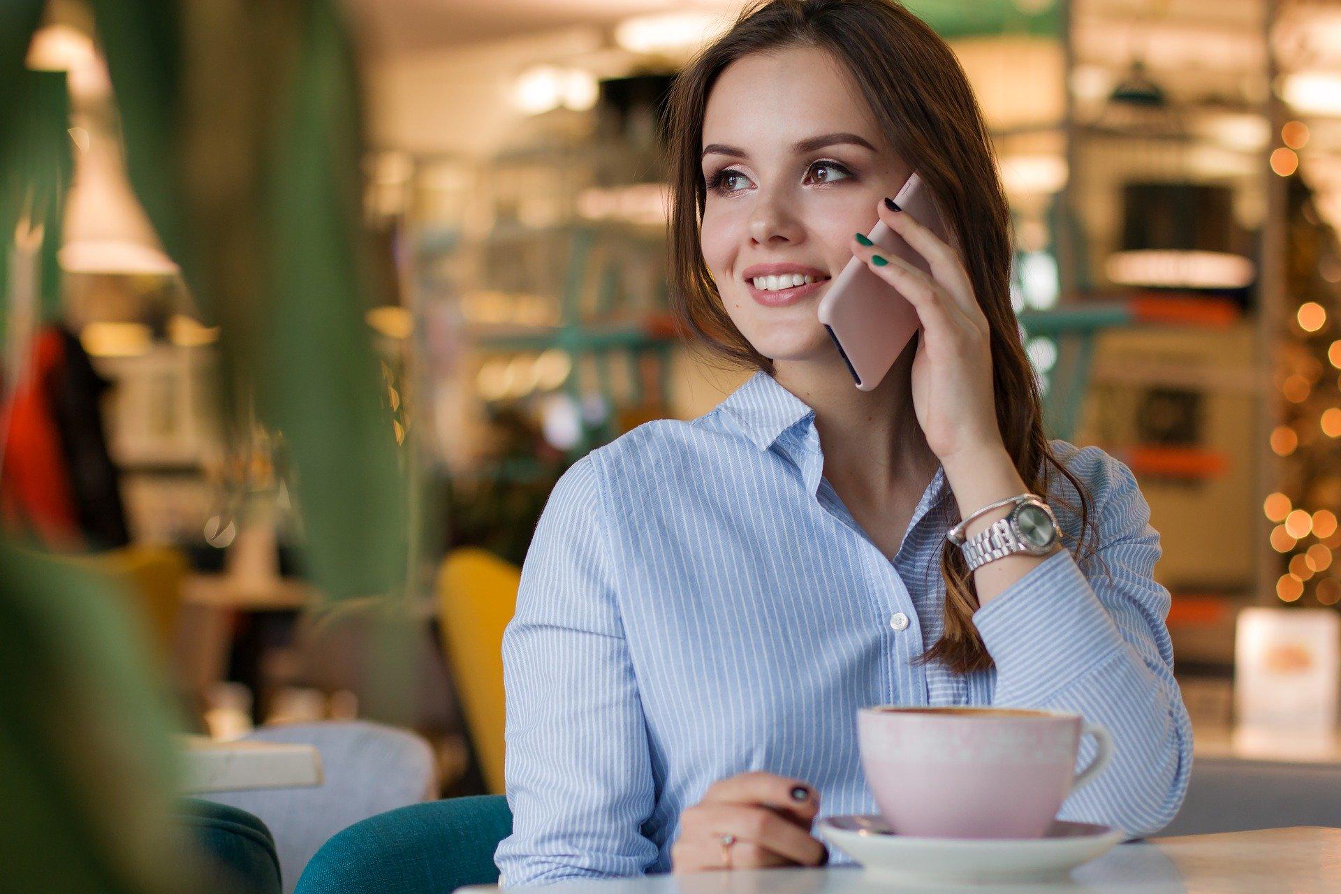 カフェでスマートフォンを耳に当て微笑む女性。