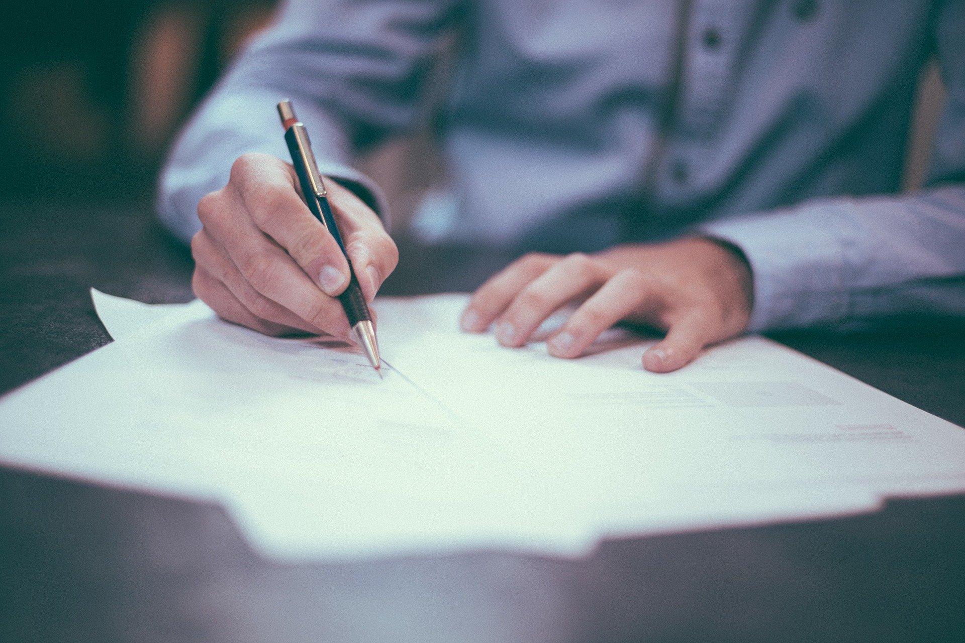テーブルで書類を書く男性の手元。