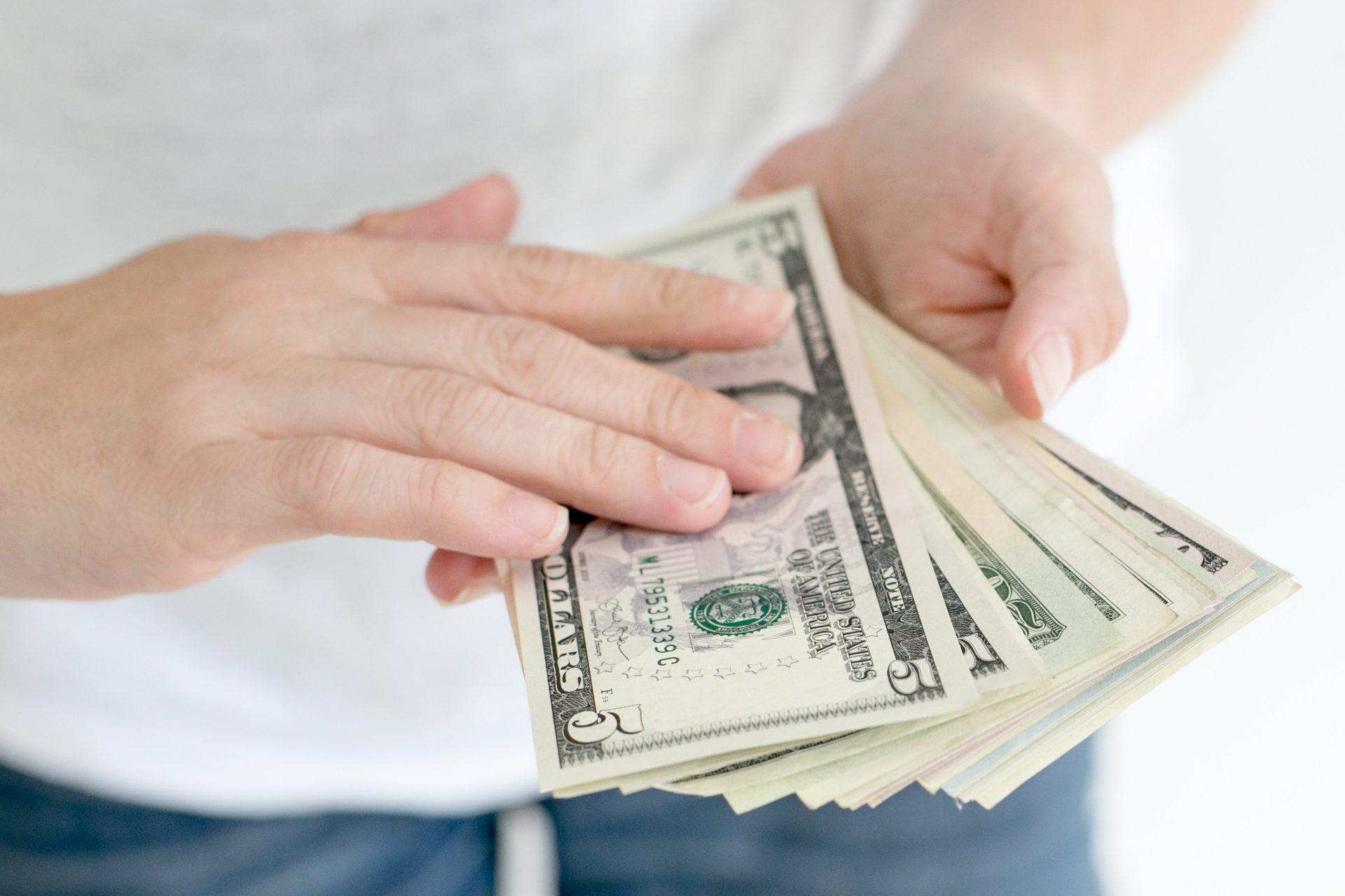 紙幣を数える男性の手元。Tシャツにジーパン。