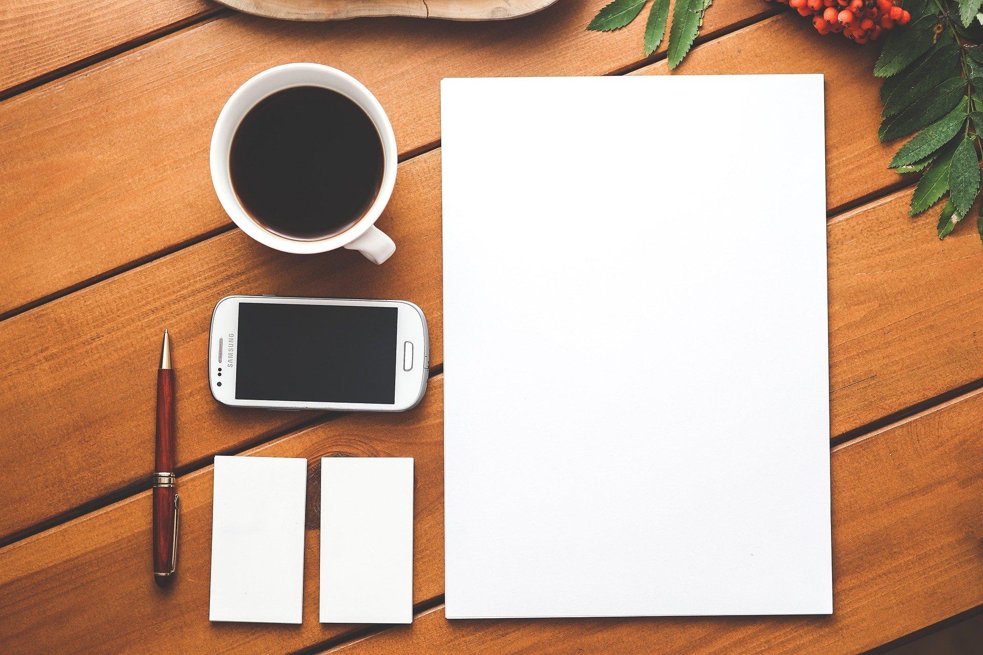 テーブルに置かれた白紙とペン、メモ帳、スマホ、コーヒー。