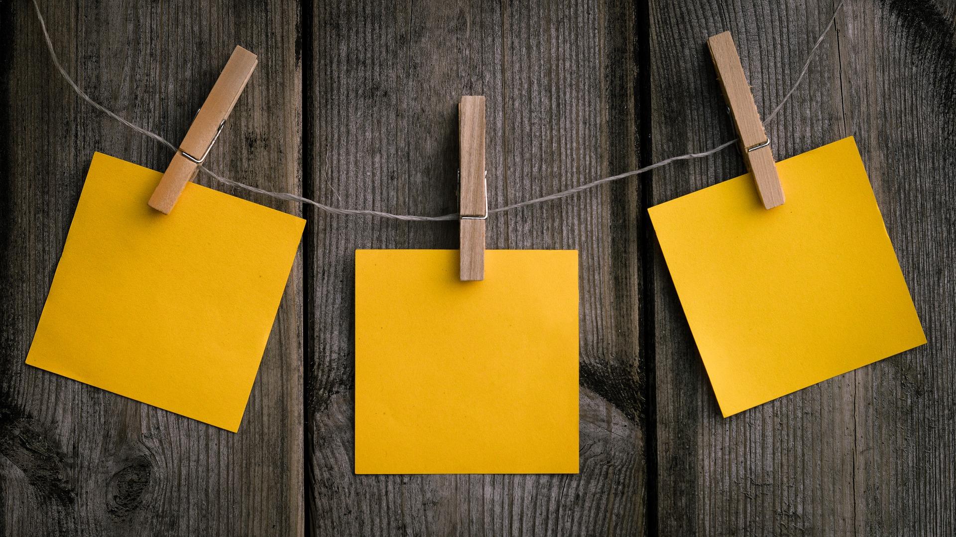 3枚のメモ紙が木製の洗濯ばさみで壁にかかったヒモに挟まれている。