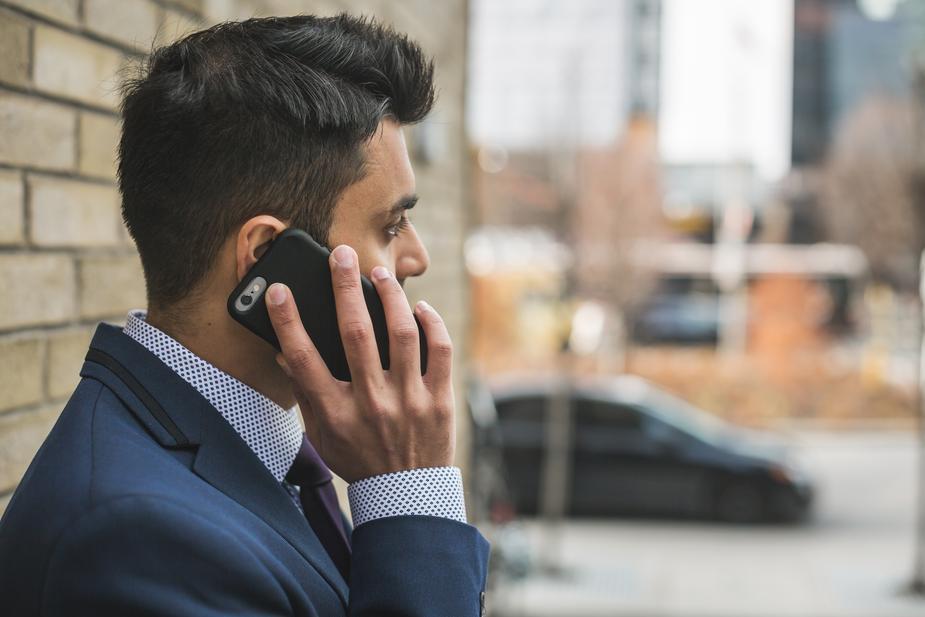 街中でスマートフォンで電話するビジネスマン