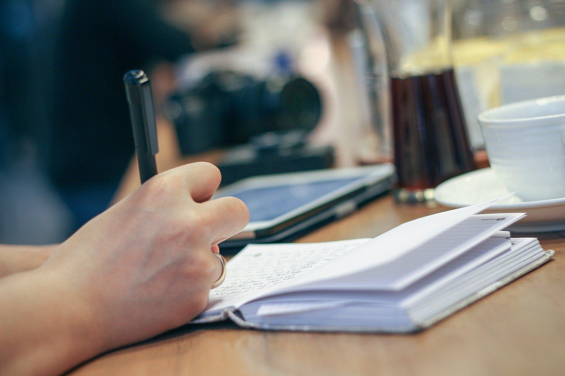ノートにペンで書きつける手元。背景にタブレット端末とコーヒー