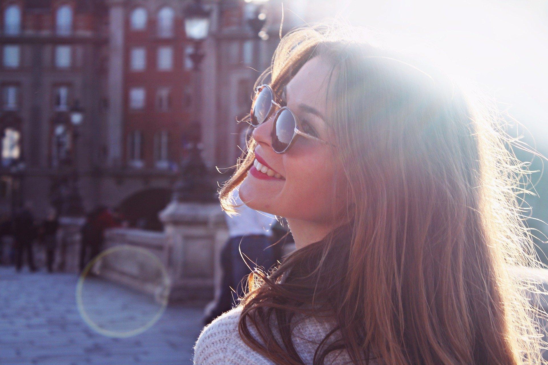 街中で笑顔で振り返るサングラスの女性。