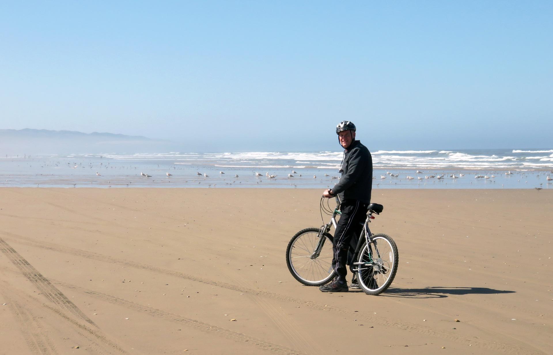 海辺で自転車に乗るシニア男性