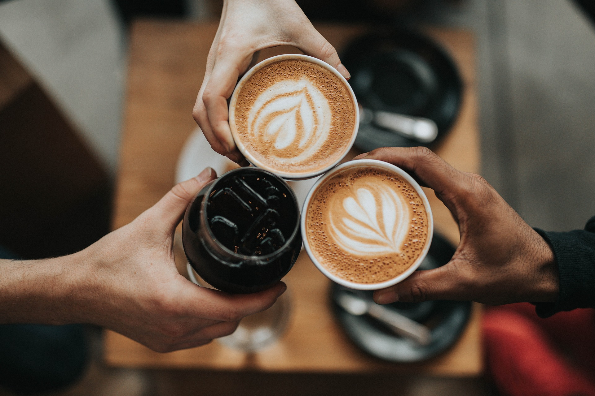 コーヒーで乾杯する三人の手元