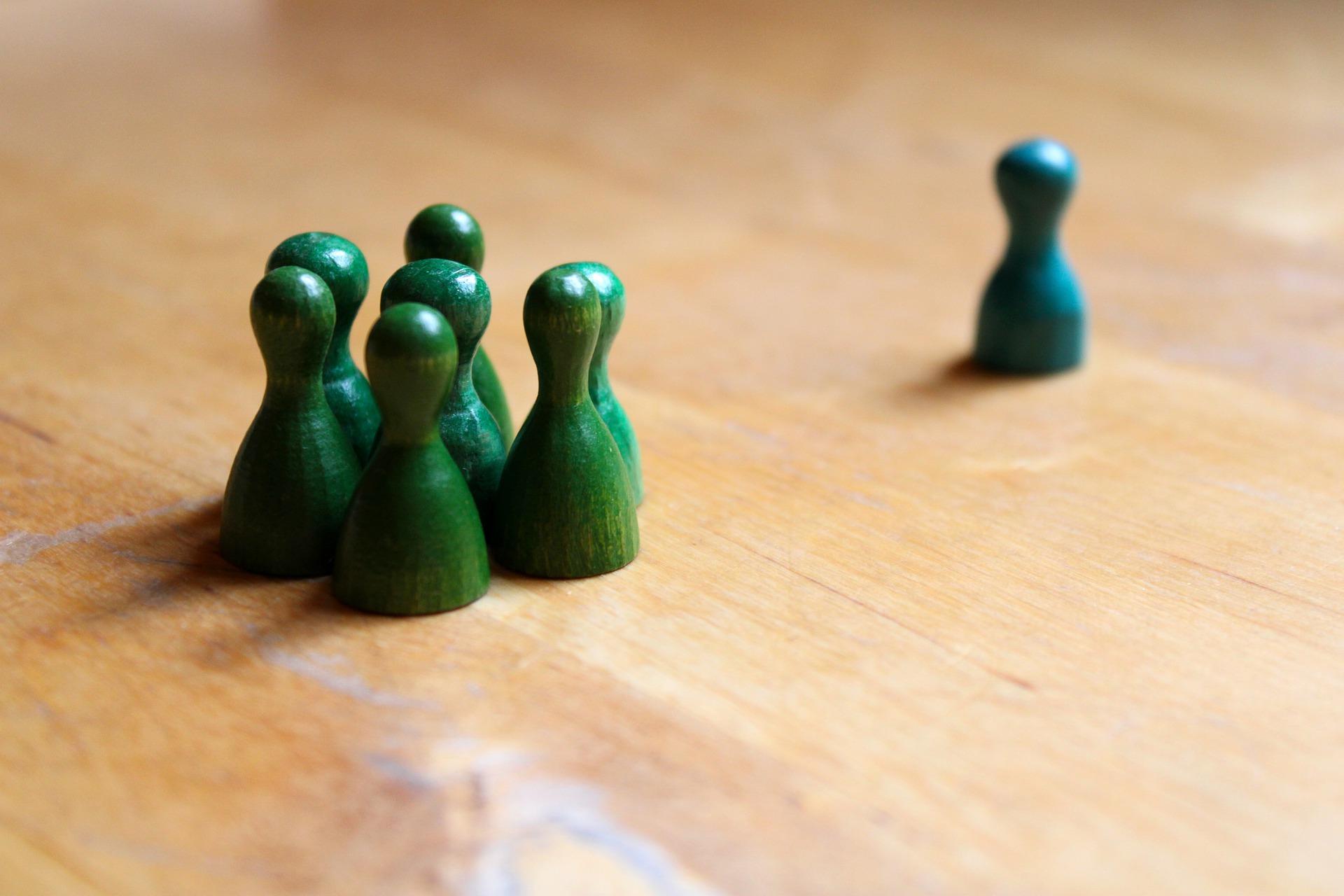 人型の木の駒が6体の集団と孤立した1体に分かれている。