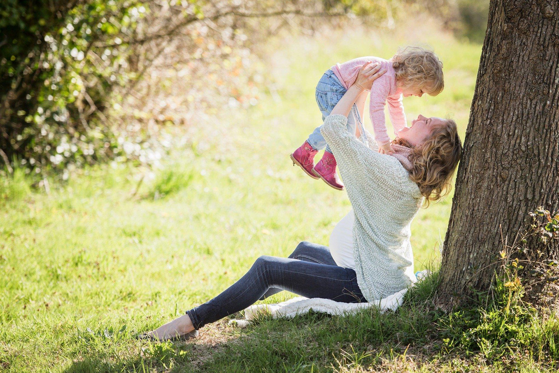 晴れた草原の木陰で幼い女の子を抱き上げる笑顔の女性