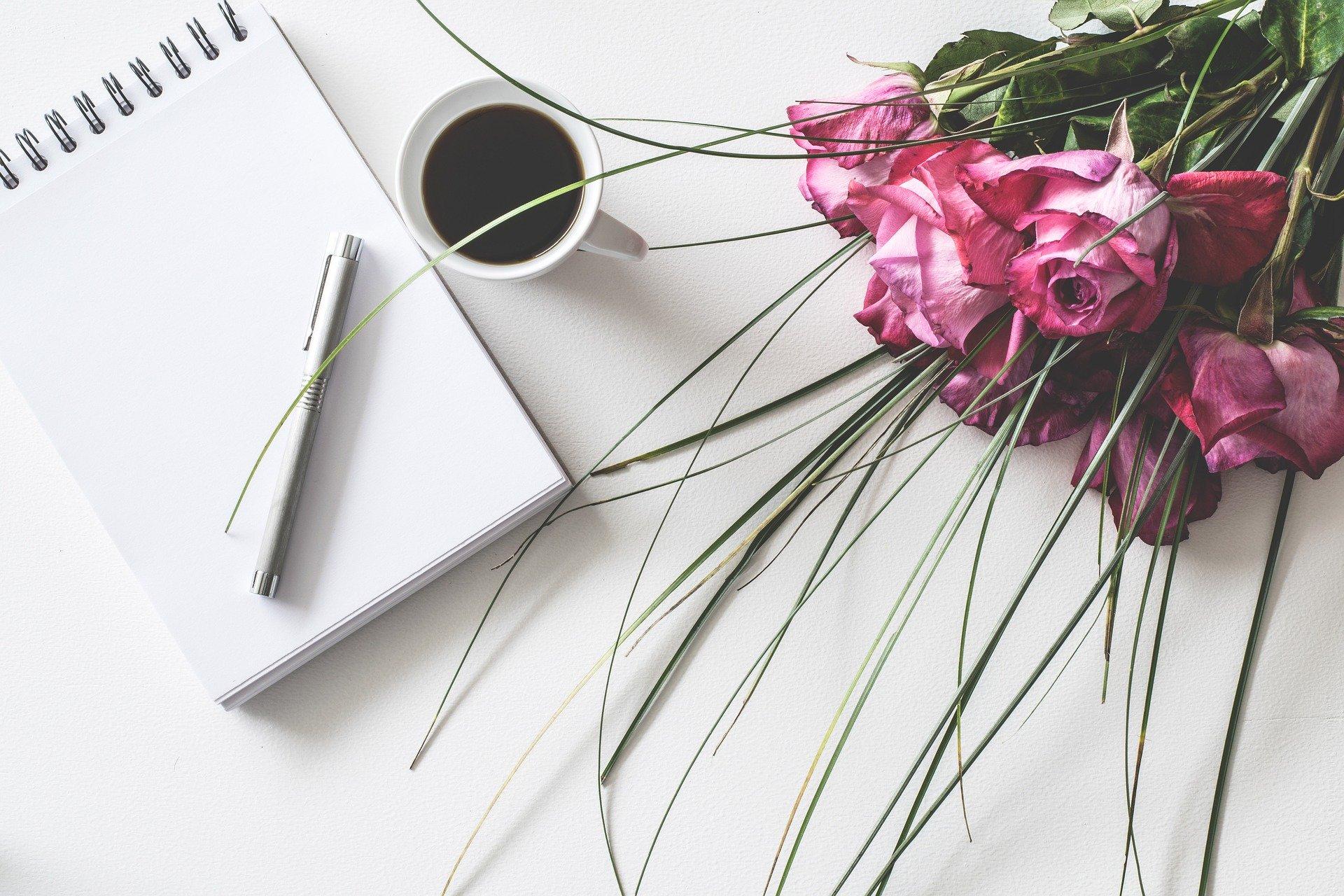 テーブルの上にノートとペン、コーヒー、バラの花束