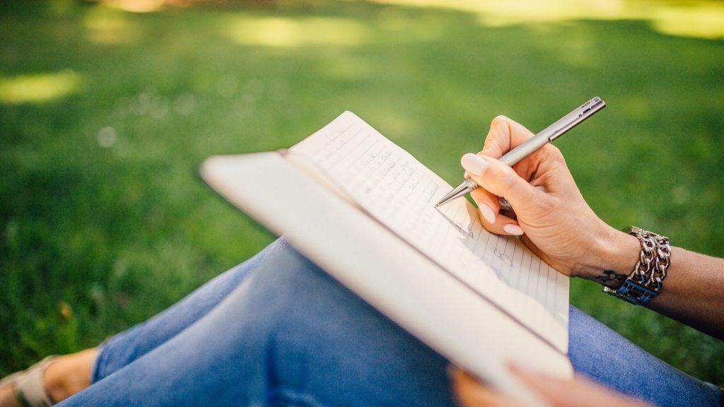 晴れた日の芝生の木陰に座ってノートにペンで書く女性の手元