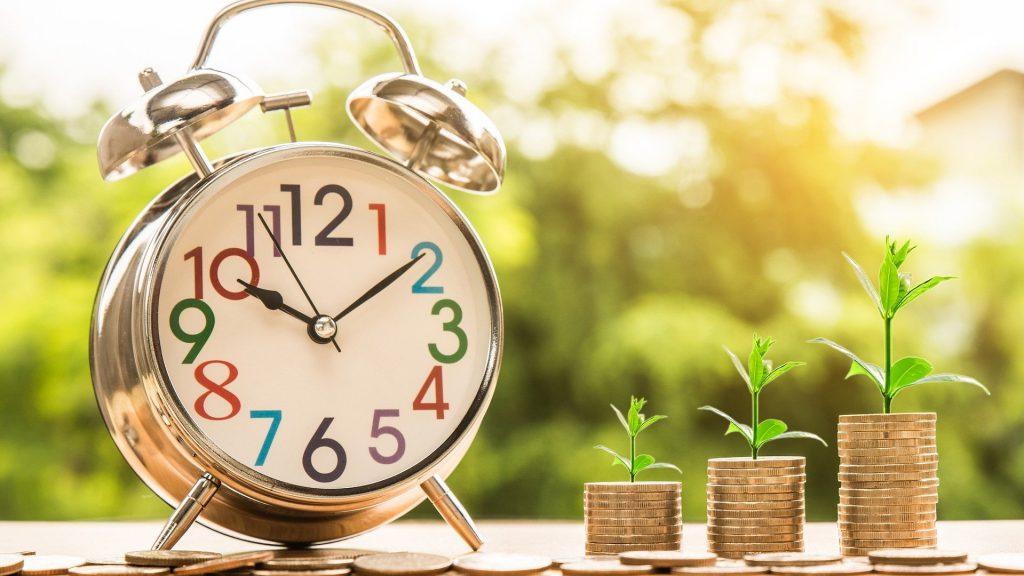 左に目覚まし時計、右に新芽の生えたコインの山