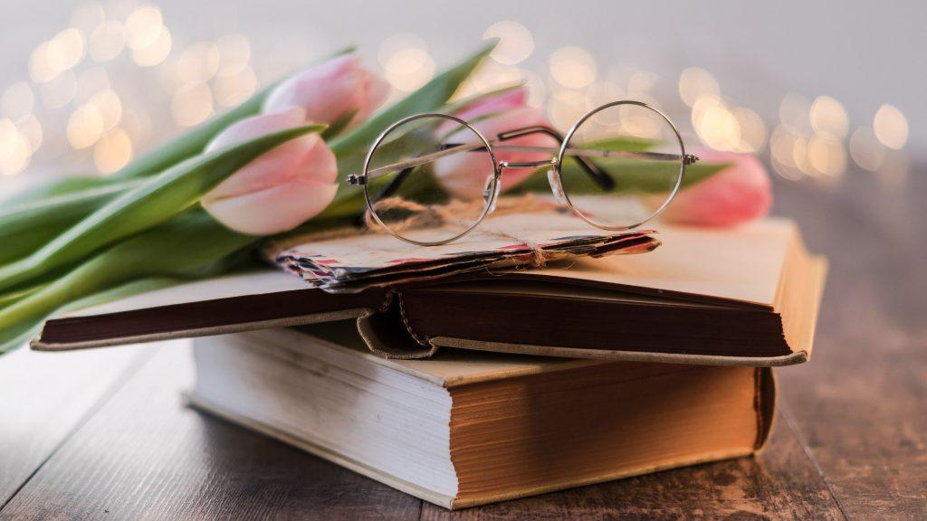 テーブルの上に本・手紙・チューリップ・丸眼鏡が重ねて積んである。
