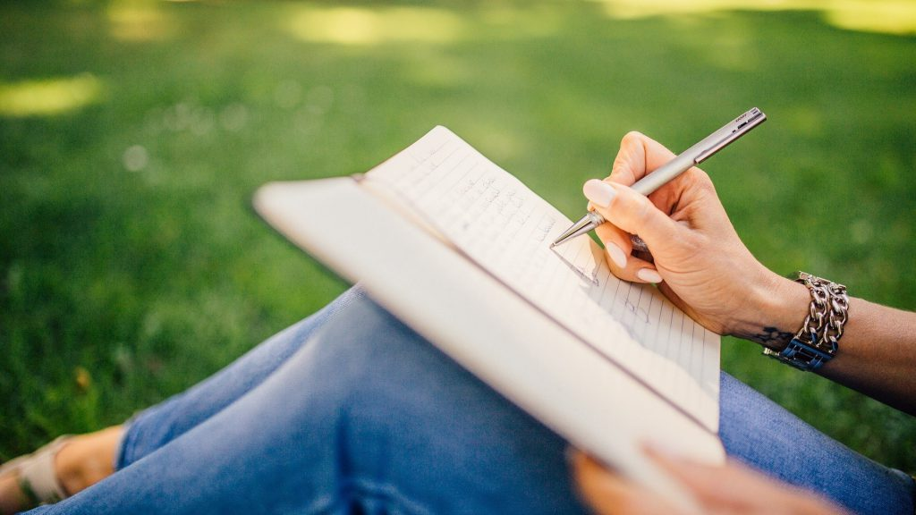 晴れた草原に座りノートに書き込む女性の手とノート載せた脚