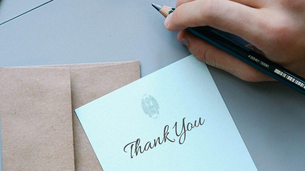 テーブルの上に「Thank you」と書かれた手紙と、鉛筆を持つ男性の手元