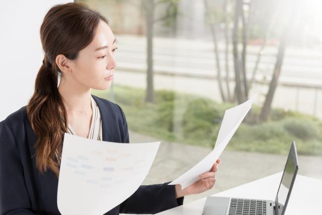 書類を見比べる女性