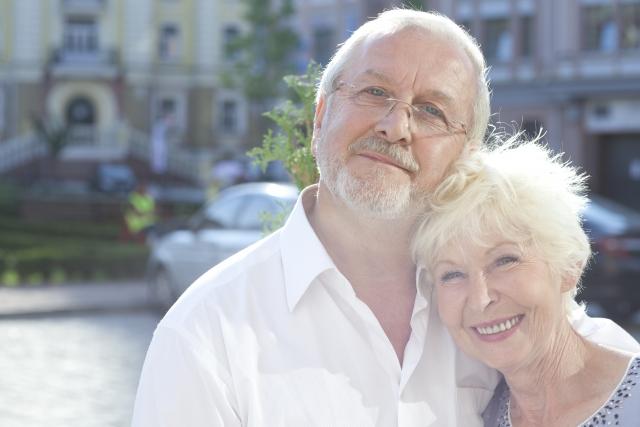 屋外で寄り添う外国人の老夫婦
