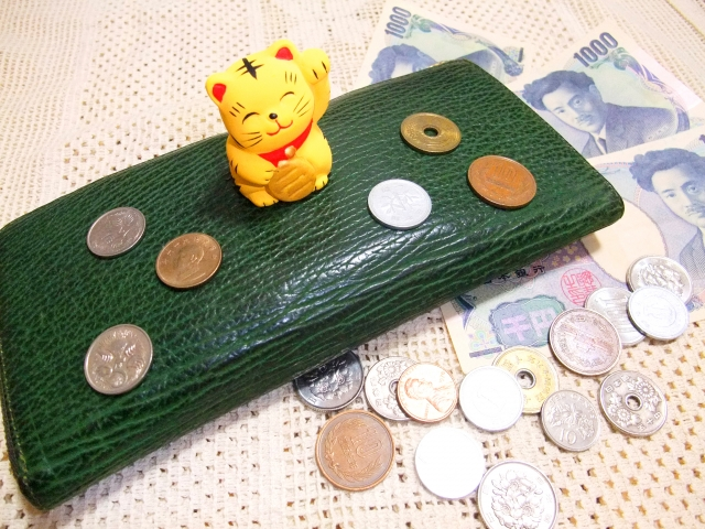 お金と財布の上に乗せた招き猫