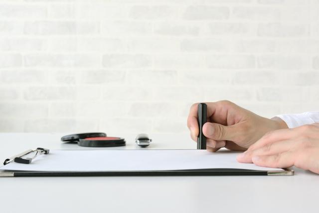書類に捺印しようとしている手
