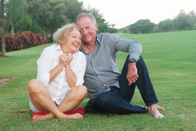 芝生の上で寄り添う外国人老夫婦